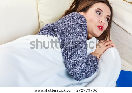 Health balance sleep deprivation concept. Sleeping woman on sofa. Girl lying on couch with book relaxed or taking power nap after lunch. - stock photo