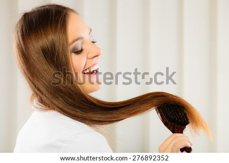 Health beauty and haircare concept - Closeup young business woman refreshing her hairstyle she brushing her long brown hair with wooden brush