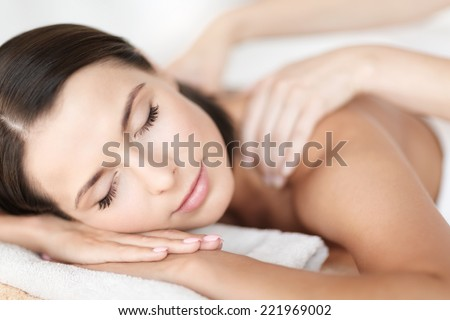 health, beauty, resort and relaxation concept - beautiful woman with closed eyes in spa salon getting massage - stock photo