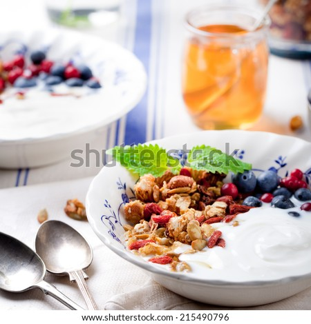 Health breakfast. Granola with pumpkin seeds and goji berries, honey, yogurt and fresh berries in a glass on blue and white background. - stock photo