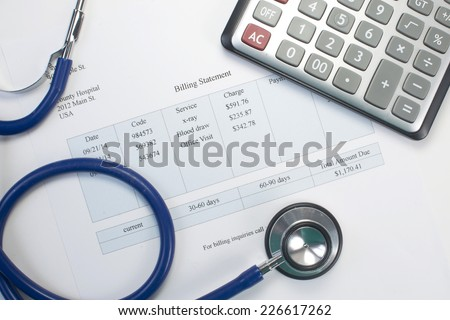 Health care billing statement with stethoscope and calculator. - stock photo