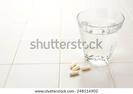 Health care concept, capsule and cup of water - stock photo