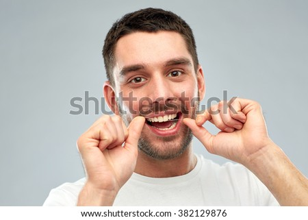 health care, dental hygiene, people and beauty concept - smiling young man with floss cleaning teeth over gray background - stock photo