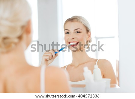 health care, dental hygiene, people and beauty concept - smiling young woman with toothbrush cleaning teeth and looking to mirror at home bathroom - stock photo