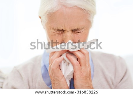 health care, flu, hygiene, age and people concept - sick senior woman blowing nose to paper napkin at home - stock photo