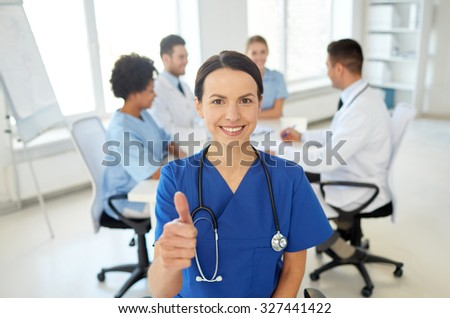 health care, gesture, profession, people and medicine concept - happy female doctor or nurse over group of medics meeting at hospital showing thumbs up gesture - stock photo