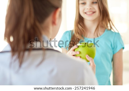 health care, healty eating, people, children and medicine concept - close up of doctor or stomatologist giving green apple to happy girl at hospital - stock photo