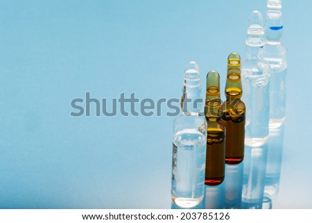 health care / medical concept: isolated set of ampules in blue background with reflection - stock photo
