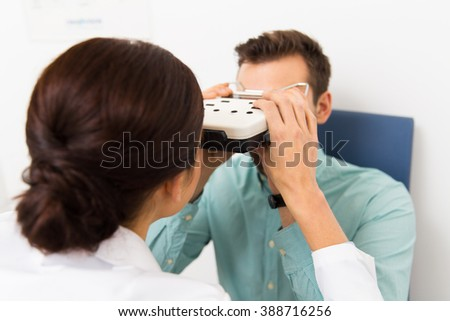 health care, medicine, people, eyesight and technology concept - close up of optometrist with pupillometer checking patient intraocular pressure at eye clinic or optics store - stock photo