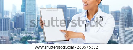health care, people and medical concept - happy african female doctor pointing finger to blank paper on clipboard over city background - stock photo