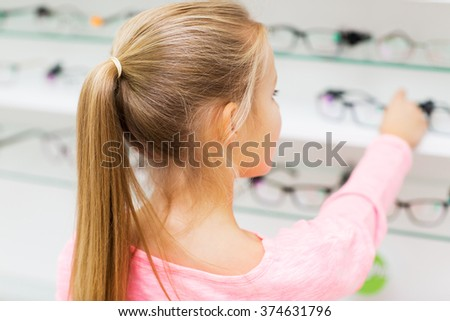 health care, people, eyesight and vision concept - close up of little girl choosing glasses at optics store - stock photo