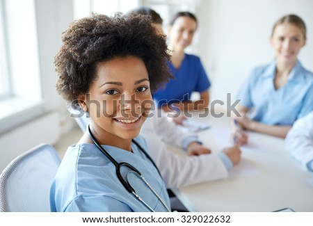 health care, profession, people and medicine concept - happy african american female doctor or nurse over group of medics meeting at hospital - stock photo