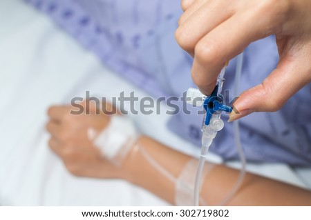 Health care series : Patient's hand adjust iv hose by herself - stock photo