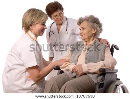 Health care workers and elderly woman in wheelchair - stock photo