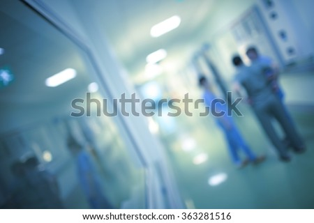 Health care workers are discussing in the hospital corridor, blurred. - stock photo