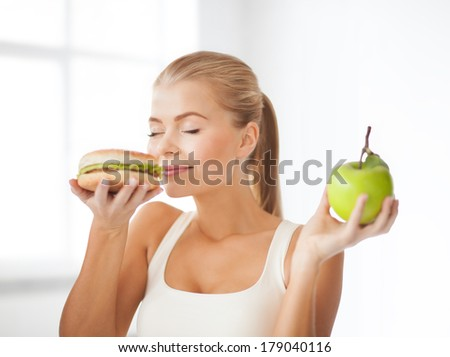 health, diet and food concept - healthy woman smelling hamburger and holding apple - stock photo