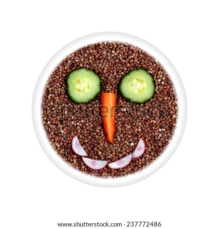 Health food - buckwheat with vegetable smiling face - eyes cucumber, carrot nose, mouth radish in circle isolated on white background - stock photo