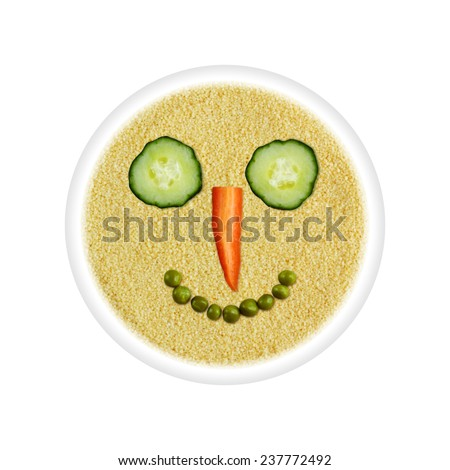 Health food - couscous with vegetable smiling face - eyes cucumber, carrot nose, mouth green peas in circle isolated on white background - stock photo
