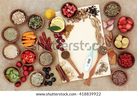 Health food selection for cold remedy to boost immune system, high in antioxidants, anthocyanins, minerals and vitamins with thermometer on natural hemp notebook. - stock photo
