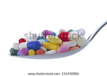Health - Heap of capsules and tablets in a spoon - stock photo