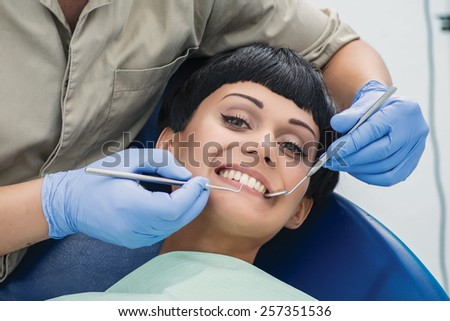 Health in a smile. Dentist makes the process of treatment of a beautiful young girl. The dentist checks the teeth of the patient and the looks in camera - stock photo