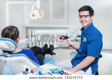 Health in a smile!Successful and smiling dentist treats teeth of a young patient and holding boron machine and looks straight into the camera. - stock photo