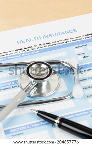 Health insurance application form with pen and stethoscope concept for life planning - stock photo