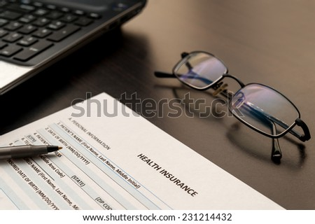 Health insurance form on a wooden table with glasses and laptop - stock photo