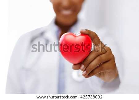 health, medicine and charity concept - close up of african american female doctor hands holding red heart - stock photo