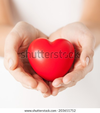 health, medicine and charity concept - close up of female hands with small red heart - stock photo