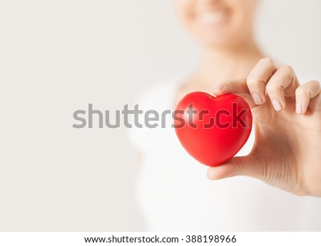 health, medicine and charity concept - close up of happy woman with small red heart - stock photo