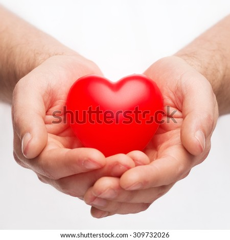 health, medicine and charity concept - close up of male hands with small red heart