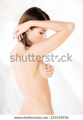 health, medicine, beauty concept - woman checking breast for signs of cancer - stock photo