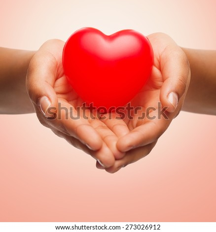 health, medicine, love, valentines day and charity concept - close up of african american female hands holding small red heart over beige background