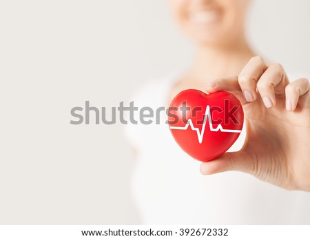 health, medicine, people and cardiology concept - close up of happy woman with cardiogram on small red heart - stock photo