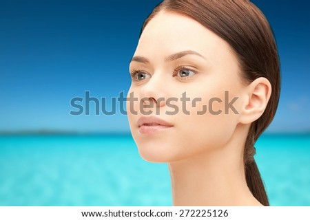 health, people and beauty concept - beautiful young woman face over blue sea and sky background - stock photo