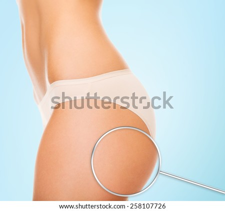 health, people, bodycare and beauty concept - close up of woman buttocks and magnifier over blue background - stock photo