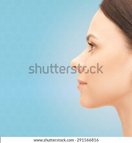 health, people, plastic surgery and beauty concept - beautiful young woman face over blue background - stock photo