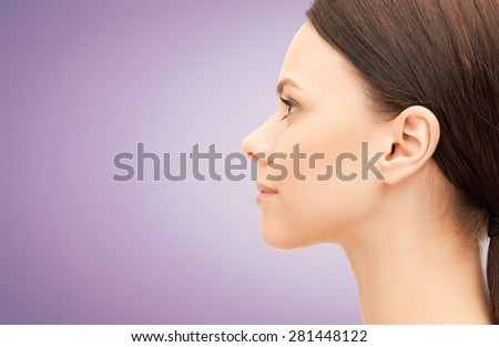 health, people, plastic surgery and beauty concept - beautiful young woman face over violet background - stock photo