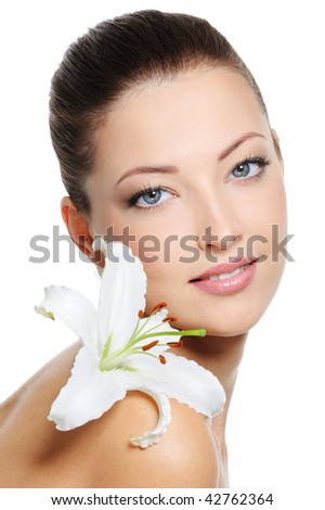 Health skin of beautiful young woman with lily on shoulder over white background - stock photo
