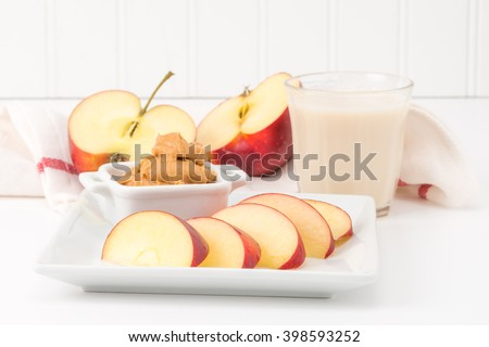 Health snack of fresh red apple and peanut butter with a glass of milk. - stock photo