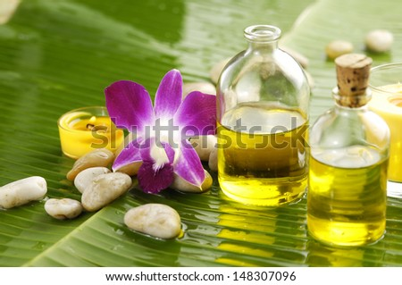 Health spa with massage oil and pink orchid on leaf - stock photo