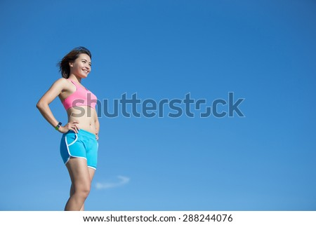 Health sport woman wearing smart watch device with touchscreen doing exercises with blue sky, asian beauty - stock photo