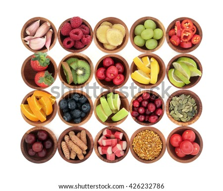 Health super food selection for cold and flu remedy high in antioxidants, anthocyanins  and vitamins in wooden bowls over white background. - stock photo