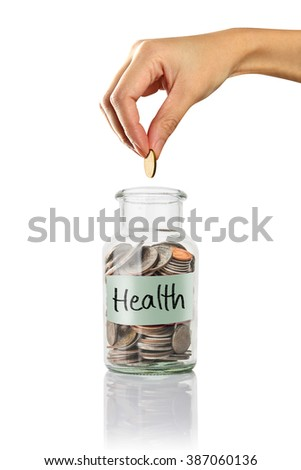 health  text, Hand putting a coin into jars. - stock photo