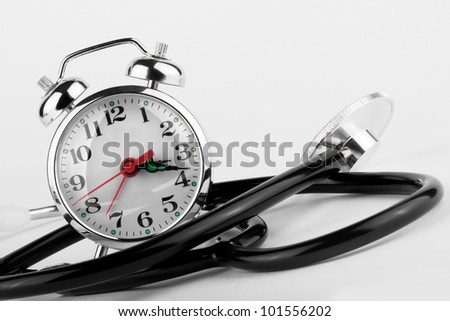 Health Time Medical concept. Alarm clock with stethoscope on a white background