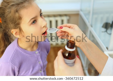 health worker giving girl syrup medicine spoon - stock photo