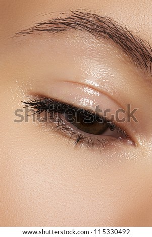 Healthcare and cosmetics. Part of female face. Closeup of woman's eye with natural makeup. Moisturizing gel on eyelid. - stock photo