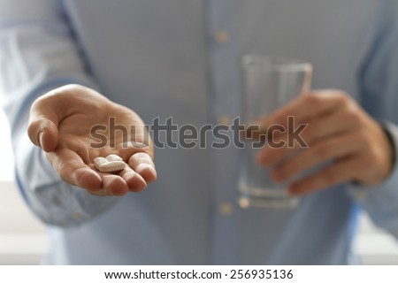 Healthcare and medical concept. Close-up view of man holding pills in one hand and glass of water in the another hand - stock photo