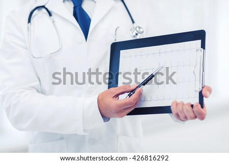 healthcare and medical concept - male doctor hands holding cardiogram - stock photo